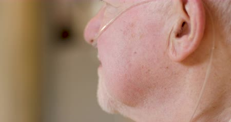 семидесятые годы : Closeup profile of an elderly senior man in his 70s or 80s wearing a supplemental nasal oxygen tube