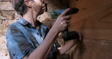 trabalhador manual : Masculine woman in her 40s preparing to drill a hole with a cordless drill power tool
