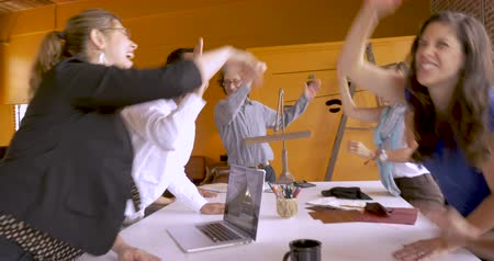 birleşik : Collaborative startup business team of mostly women celebrate with high fives and finish with a fist bump in their open space office Stok Video