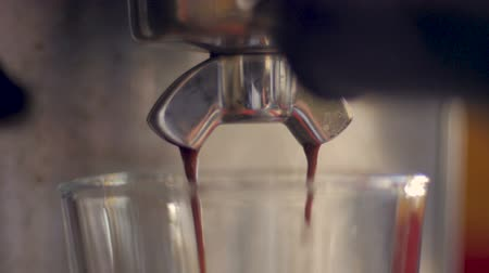 Steaming hot espresso coffee dripping from a stainless steel machine - close up
