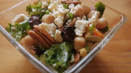jarmuż : Push in of a healthy vegetarian kale, pecan nut, garbanzo, cranberry and cheese salad in a square glass bowl