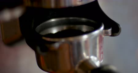Extreme close up of coffee grounds filling up a portafilter in an espresso machine Stok Video