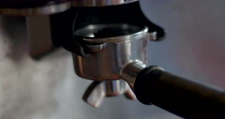 grãos de café : Close up of a hand adding fresh ground coffee and packing it in a portafilter in espresso machine