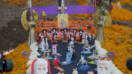 muertos : Decorated alter with sugar skulls, marigold flower petals and skeletons at a grave during day of the dead in Mexico Stock Footage