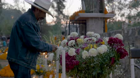 muertos : TZURUMUTARO, MEXICO - NOVEMBER 1, 2016 - Old Mexican man in a cowboy hat lighting candles at an alter at a graveyard during day of the dead Stock Footage