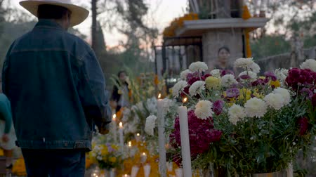 muertos : TZURUMUTARO, MEXICO - NOVEMBER 1, 2016 - Friendly people greeting each other while an old man lights candles at a graveyard alter during day of the dead Stock Footage