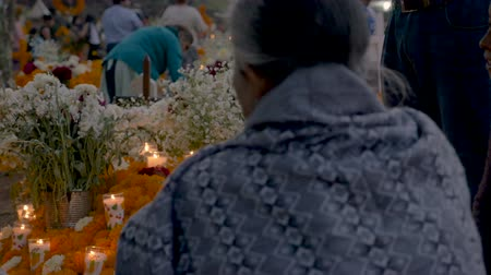 marigolds : TZURUMUTARO, MEXICO - NOVEMBER 1, 2016 - Dolly shot of people sitting and talking at a graveyard decorating alters and celebrating their lost loved ones during day of the dead