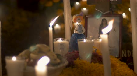 muertos : TZURUMUTARO, MEXICO - NOVEMBER 1, 2016 - Katrina figurine, photo of a deceased woman, and candles at a grave during day of the dead Stock Footage