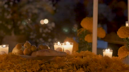muertos : Tilt up of a typical grave with fruit offerings, marigold flower petals and candles during day of the dead in Mexico