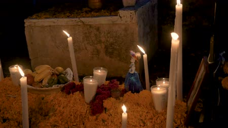 muertos : Fresh fruit used as an offering, a Katrina figurine, and candles on top of a grave during day of the dead in Mexico - dolly shot Stock Footage