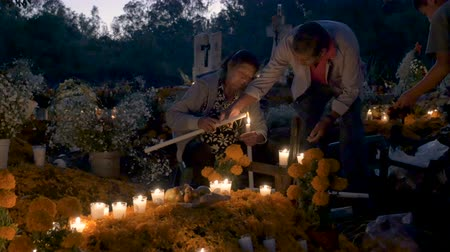 muertos : TZURUMUTARO, MEXICO - NOVEMBER 1, 2016 - Happy elderly Mexican woman lighting a candle with her multi generational family at a grave during day of the dead - dolly shot