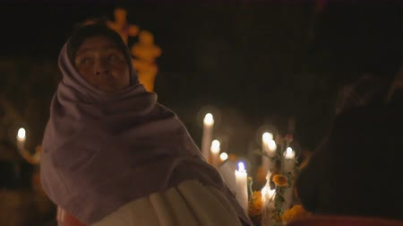 muertos : TZURUMUTARO, MEXICO - NOVEMBER 1, 2016 - Woman wearing a scarf over her head at night sitting by candles at a grave during day of the dead