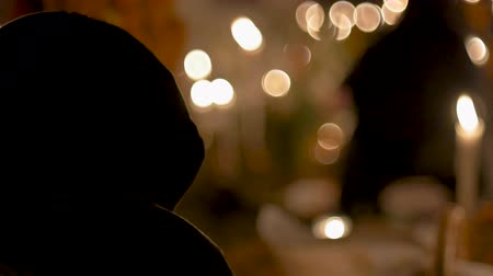 Person covered with a hoodie or scarf sitting by candle light at night in a church or ceremony with bokah