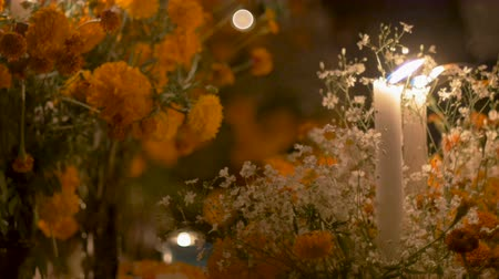 luto : White candles burning at night next to marigold flowers during day of the dead in Mexico - dolly shot Stock Footage
