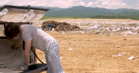 Man throwing old water damaged carpet away at a landfill out of a pickup truck