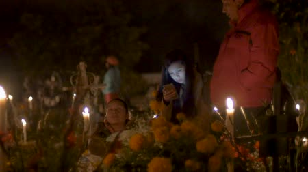TZURUMUTARO, MEXICO - NOVEMBER 1, 2016 - Young womans glowing face is illuminated using cell phone at cemetery with her family at day of the dead