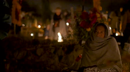 TZURUMUTARO, MEXICO - NOVEMBER 1, 2016 - Single old woman sitting in a cemetery alone during day of the dead at night illuminated by candles Stok Video