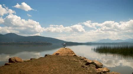 A man sits at the edge of an old pier on a mountain lake and enjoys the view - wide shot