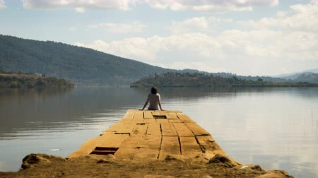 tek başına : Tourist man relaxing at the edge of a dock alone on a mountain lake on a beautiful summer day - medium shot