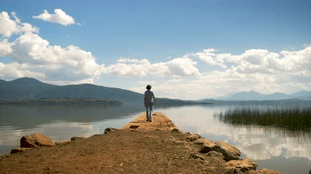 A single traveling man walks to the edge of a old pier overlooking a mountain lake Wideo