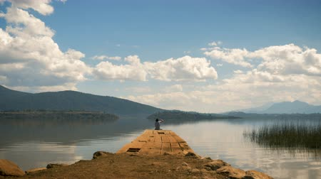 Man sitting at the edge of a dock on a beautiful peaceful mountain lake shielding his eyes and taking in the view Wideo