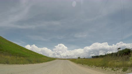 POV wide angle driving on a gravel country road alongside grassland during the summer
