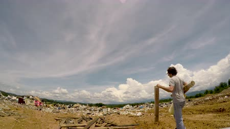 Man throwing misc trash away in a landfill junkyard dump - wide angle Stok Video