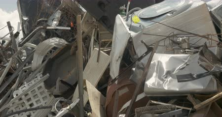 Large pile of scrap metal, broken, and discarded appliances at a junkyard, landfill, or recycling center - dolly shot