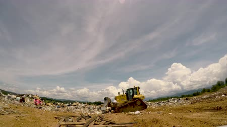 ALEXANDER, NC, UNITED STATES - CIRCA MAY 2017 - Caterpillar bulldozer driving across a pile of trash in a landfill dump