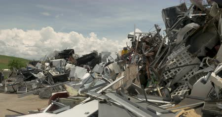Wide shot of a piece of household garbage being thrown into a pile of recycled metal at a recycling center, junkyard, landfill, or transfer station.