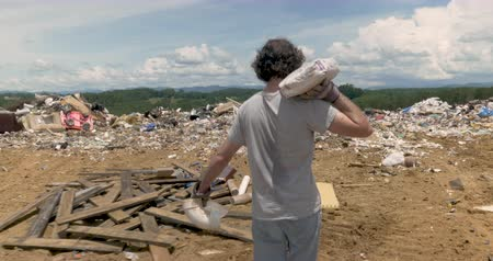 ALEXANDER, NC, UNITED STATES - CIRCA MAY 2017 - Man throwing away construction trash away at a landfill or junkyard