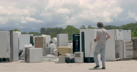 Man carrying a broken dehumidifier into a pile of discarded kitchen appliances at a landfill, junkyard, recycling center, or transfer station