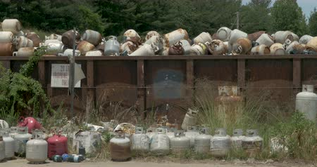 ALEXANDER, NC, UNITED STATES - CIRCA MAY 2017 - Abandoned 20 lb propane tanks in an overflowing dumpster at a recycling center, landfill, or transfer station