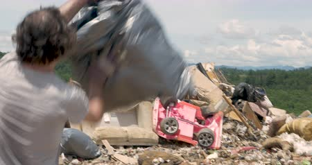 Man throwing a bag of trash and a broken office chair into the landfill