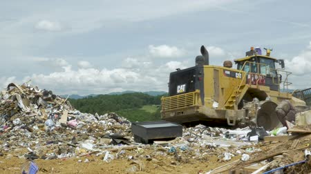 ALEXANDER, NC, UNITED STATES - CIRCA MAY 2017 - Large heavy machinery moving back and forth over a pile of trash at a landfill Stok Video