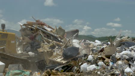 ALEXANDER, NC, UNITED STATES - CIRCA MAY 2017 - Caterpillar bulldozer landfill compactor pushing household trash, old mattresses, and discarded furniture Stok Video