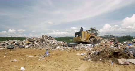 ALEXANDER, NC, UNITED STATES - CIRCA MAY 2017 - Caterpillar bulldozer working at a landfill to eliminate trash Stok Video