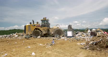 ALEXANDER, NC, UNITED STATES - CIRCA MAY 2017 - Caterpillar bulldozer pushing and burying trash at a landfill Stok Video