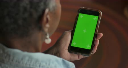 Older attractive senior black woman in her 50s or 60s looking at her smart phone technology with a chroma key green screen - OTS rack focus Stok Video