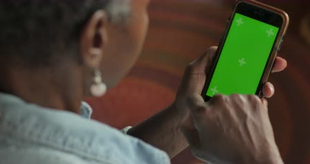 African American senior retired woman in her 50s or 60s scrolling up and down on her green screen mobile phone - OTS