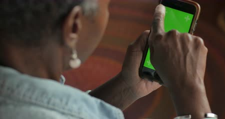 Older attractive senior black woman in her 50s or 60s double tapping a green screen phone in a vertical position - OTS Stok Video