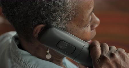 Older black woman in her 50s or 60s with short black and gray hair talking on a cordless landline phone - OTS Stok Video