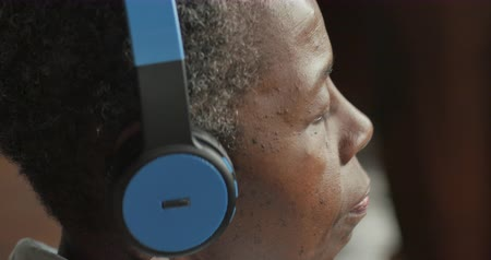 Youthful attractive healthy black senior woman in her 50s or 60s listening to music with headphones - profile Stok Video