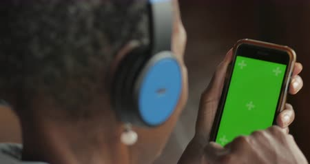 Elderly senior black woman selecting music from her green screen smart phone mobile app streaming service - OTS Stok Video
