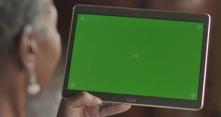 Happy senior black woman in her 50s or 60s using technology, swiping and tapping a green screen digital tablet - OTS