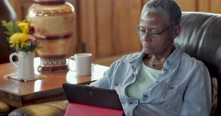 Attractive elderly black woman in her 50s or 60s using a digital tablet in her living room - dolly shot
