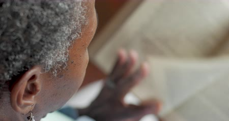művelt : Senior black woman in her 50s or 60s reading a paper book and turning the pages - OTS