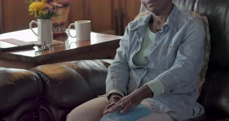 mračící : Tilt up of an elderly senior black woman in her 50s or 60s using an ice pack on her knee to relieve pain and swelling in her home Dostupné videozáznamy