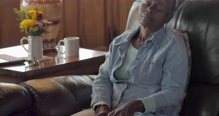 штамм : Attractive elderly senior black woman in her 50s or 60s feeling relief from icing her knee with an ice pack while sitting on her living room sofa during the day