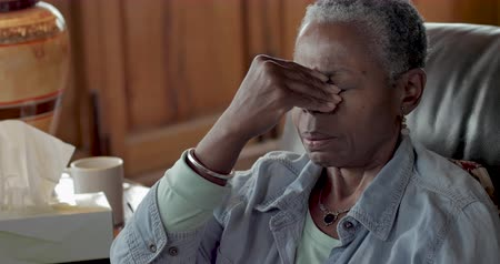 mračící : Elderly senior black woman rubbing her forehead to relieve headache pain from a sinus cold, allergies, or flu symptoms
